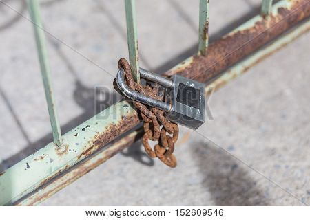 Old Lock With Chain On Steel Wall.