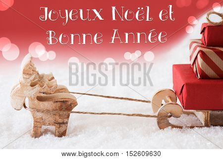 Moose Is Drawing A Sled With Red Gifts Or Presents In Snow. Christmas Card For Seasons Greetings. Red Christmassy Background With Bokeh Effect. French Text Bonne Annee Means Happy New Year