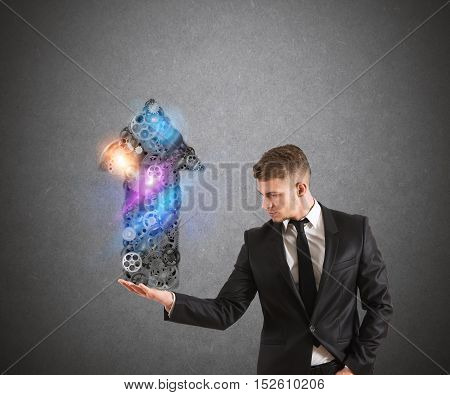Businessman holds a system of gears that form an arrow