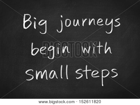 big journeys begin with small steps concept text on blackboard background
