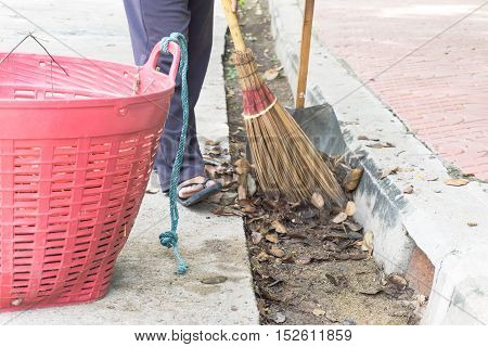 Road sweeper worker cleaning city street with broom tool.