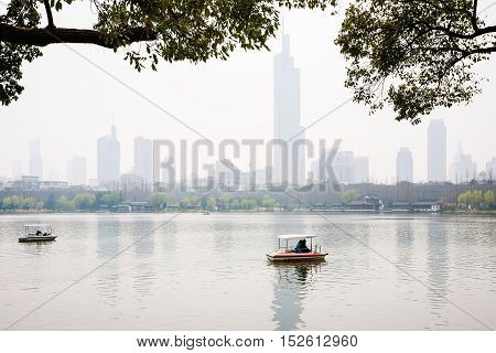 romantic scene of a foggy lake with boats in Nanjing China