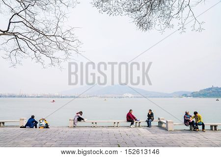 NANJING CHINA- MARCH 17: Chinese people sitting and talking by Xuanwu lake tourist area in the afternoon on March 17 2016 in Nanjing.