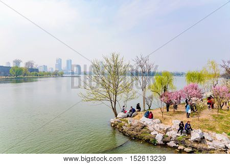 NANJING CHINA- MARCH 17: Chinese tourists on Xuanwu Lake sitting and enjoying the afternoon on March 17 2016 in Nanjing.
