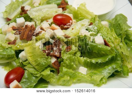 A Caesar salad croutons bacon parmesan cheese and Caesar dressing