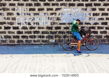 MANILA PHILIPPINES - JUNE 16: This is a street scene of the outside of a building with a no parking sign written across it and a Filipino local riding a bike on June 16th 2014 in Manila.