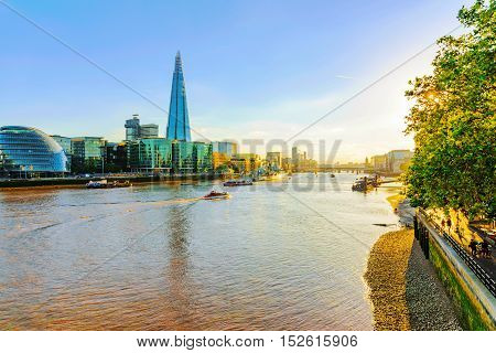 LONDON - JULY 06 2016: View of London's skyline with Shard building and the city hall in the late afternoon. Taken from tower bridge on July 06 2016 in London.