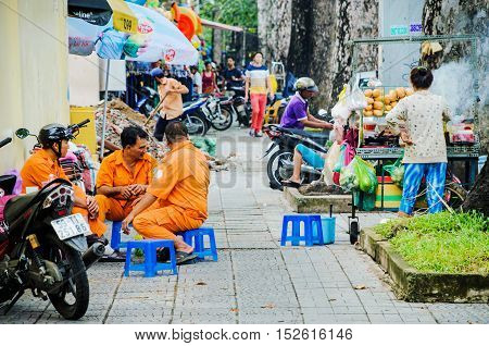 HANOI VIETNAM - JULY 19: Street scene in Hanoi of workers waiting for food from a local food stand at lunch time on July 13 2013 in Hanoi.