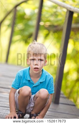 a little blonde boy kneeling outdoor with a serious facial expression