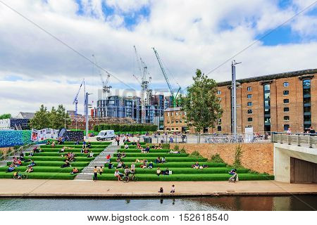 LONDON - AUGUST 22: This is a view of Granary Square with people sitting riverside along the regents canal and the Central Saint Martins university campus in the background on August 22nd 2016 in London