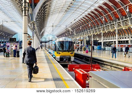 LONDON - SEPTEMBER 08: This is Paddington station's train platform with a man walking towards a train that is waiting to leave and other people in the background on September 8th 2016 in London