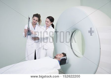 Radiologic Technician And Patient Being Scanned And Diagnosed On Ct (computed Tomography) Scanner In