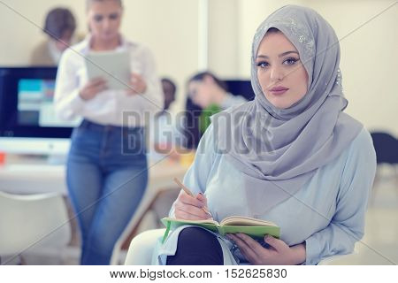 Arabian Businesswoman in office with Businesspeople meeting in the background Arabian woman wearing Hijab in office with her colleagues in background