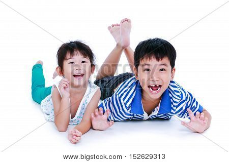 Asian kids lying prone on the floor. Chinese children having happy and smiling isolated on white background. Conceptual about loving of sibling. Happy family spending time together. Studio shot.