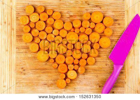 Chopped Carrots As Heart Shape Beside Knife