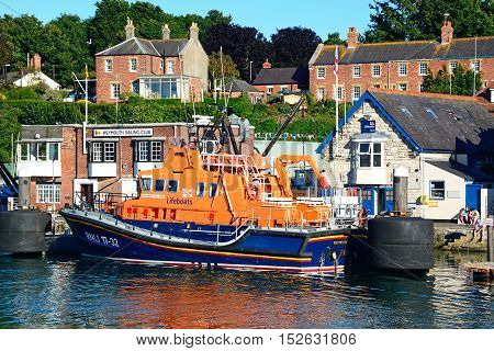 WEYMOUTH, UNITED KINGDOM - JULY 18, 2016 - RNLI lifeboat moored in the harbour with the Weymouth Sailing Club building to the rear Weymouth Dorset England UK Western Europe, July 18, 2016.