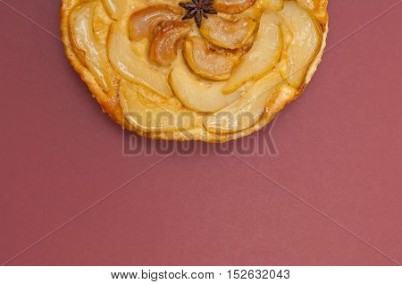 Tarte Tatin apple and pear tart pie isolated on claret background with copy space