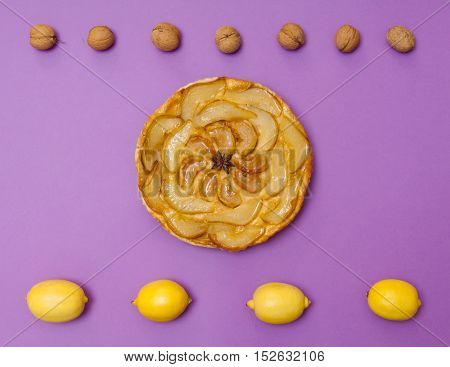 Whole tarte Tatin apple and pear tart pie with fruits on purple background with copy space