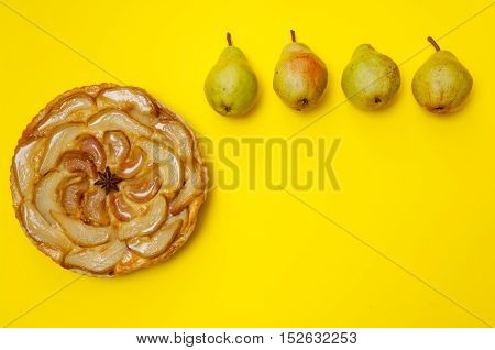 Whole tarte Tatin apple and pear tart pie with pears on yellow background with copy space