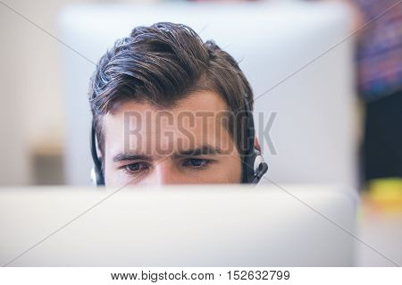 Thoughtful young programmer coding on computer in office