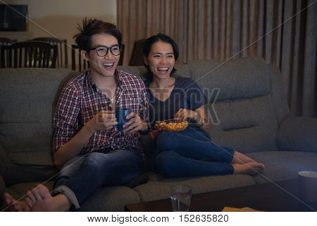 Asian young couple watching comedy movie on tv at night