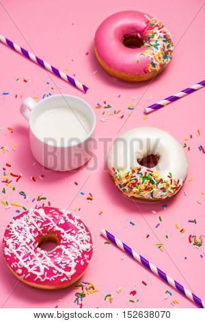 Donuts with icing and milk on pastel pink background. Sweet donuts.