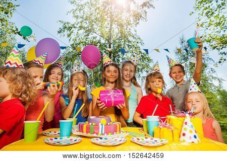 Funny kids in party hats cheering birthday girl, blowing the whistles at summer park