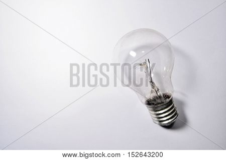 Old and dusty incandescent light bulb on white paper background