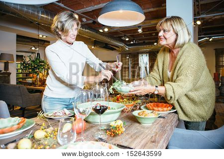 Smiling women assist one to another with dinner service at celebration table. Candid portrait.