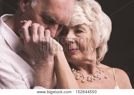 Senior Man Kissing Female Hand