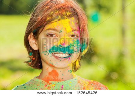 Portrait of happy smiling ten years old boy with face smeared with colored powder
