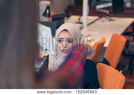 Worried Arabic Businesswoman Wearing Hijab Receiving A Notification From A Colleague In Her Workplac