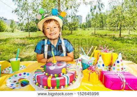 Portrait of happy smiling kid boy sitting next to the birthday cake and making a wish, at the outdoor party