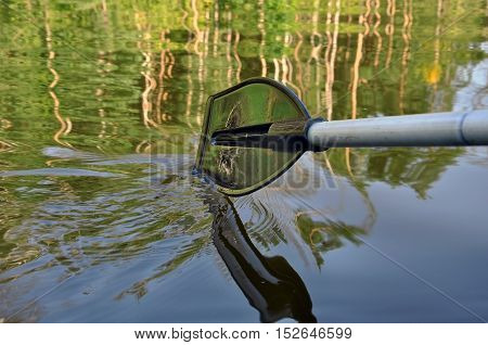 Rubber paddle touches the surface of the river water with reflection of forest.