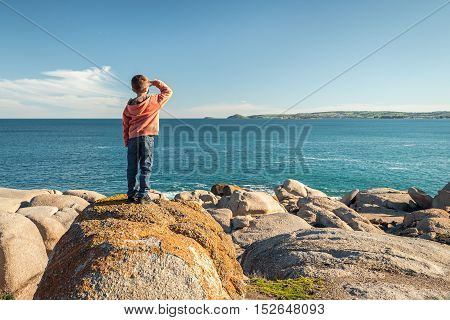 Boy standing at the edge of the rock and looking into the sea at Port Elliot South Australia. Color toning applied