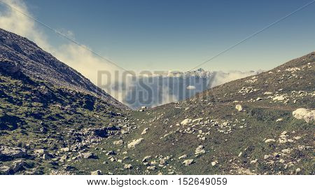 Silhouette of a person ascending a green valley. Stol mountain in Slovenia.