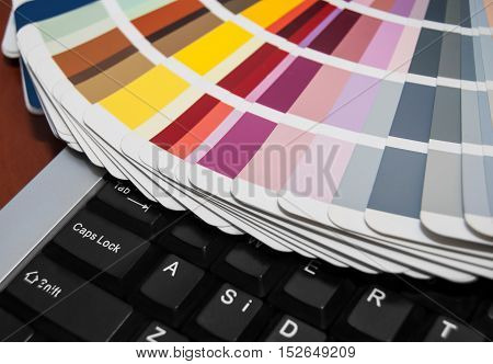 Color swatches book on a computer keyboard