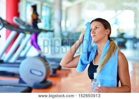 Fitness Woman. Beautiful Young Girl In The Gym Drinking Water, With Blue Towel.