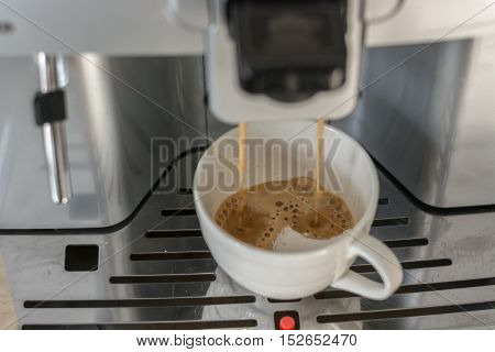 Close-up of espresso pouring from coffee machine. Professional coffee machine. Office.