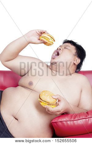 Image of fat man eating two big hamburgers on the red couch isolated on the white background