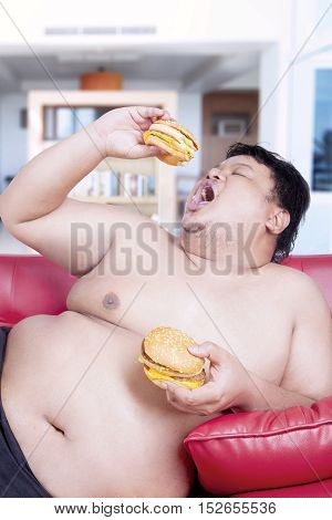 Image of a fat man holding two burgers while sitting on the red sofa at home