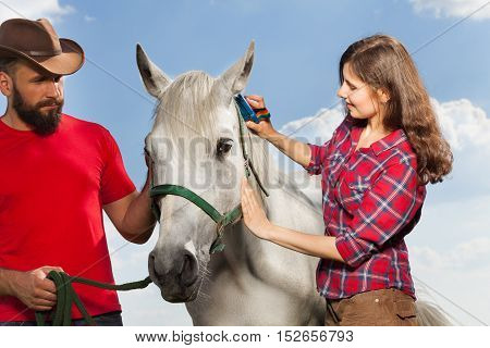 Young woman brushing beautiful white horse while man in cowboy hat holding it by a bridle