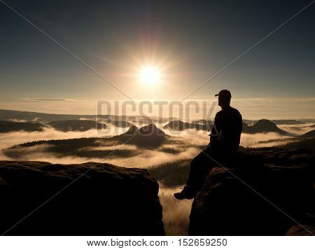 Moment Of Loneliness. Man With Cap Sit On Mountain And Watch To Fog