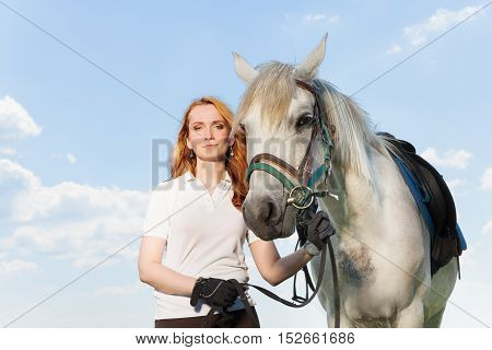Beautiful picture of pretty young woman holding white horse by the bridle, against blue sky