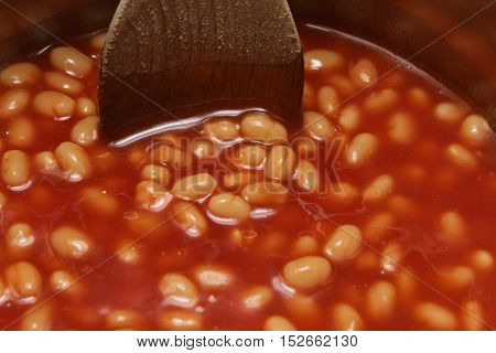 Saucepan Of Baked Beans Being Stirred With A Wooden Spoon