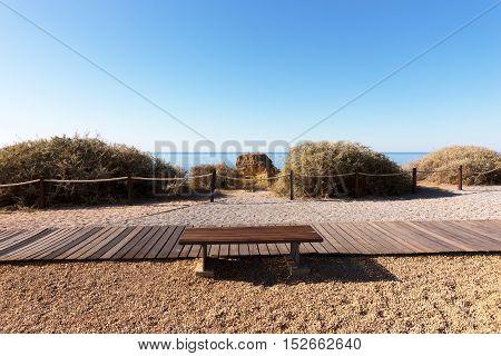 Wooden Walkway and Picnic bench at the Beach of Praia da Rocha, Algarve