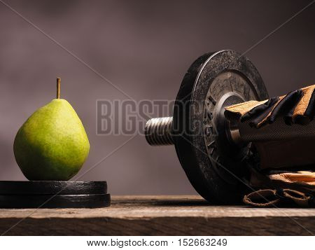 Fresh green pear with fitness sports equipment on a wooden table