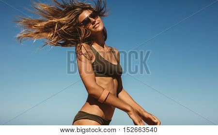 Beautiful Woman Against Blue Sky With Fluttering Hair