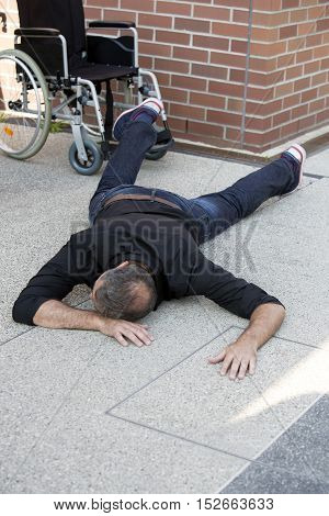 impaired man lying on street after in fell out of wheelchair