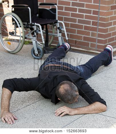 impaired man lying on the floor after falling out of wheelchair